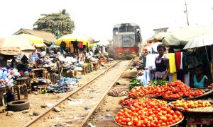 Pix shows a train struggling to have its way on its rail as traders at Agbado Crossing had already 'hijacked' the railway to display their wares. Photo by Lamidi Bamidele